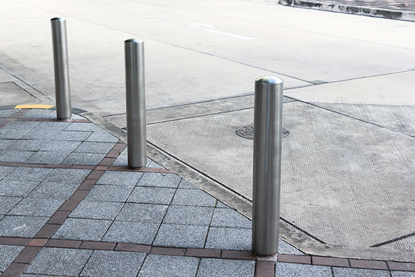 Stainless Steel bollards on grey stone pavement of car park